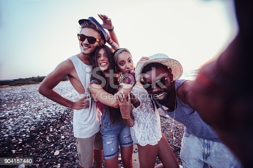 Young multi-ethnic hipster tourist friends having fun taking selfies on island beach on smartphone