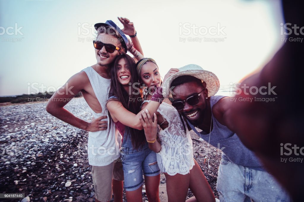 Young multi-ethnic hipster friends taking selfies on island summer vacation stock photo