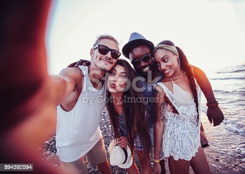 istock Young multi-ethnic hipster tourist friends taking selfies on beach 894392594
