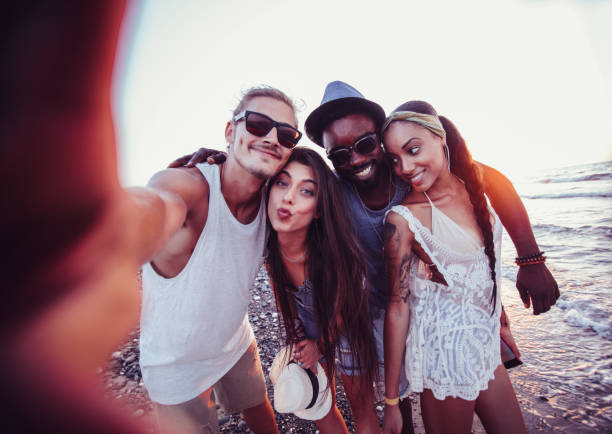 Young multi-ethnic hipster tourist friends taking selfies on beach stock photo