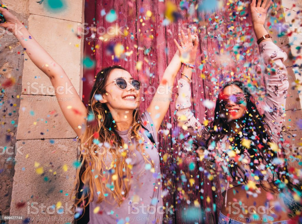 年輕的多民族時髦婦女慶祝與五彩紙屑在城市 - 免版稅20多歲圖庫照片