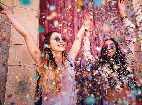 年輕的多民族時髦婦女慶祝與五彩紙屑在城市 照片檔及更多 20多歲 照片