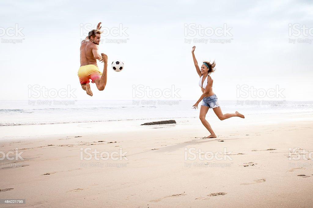 Jovem MULTIRRACIAIS casal se divertindo com o futebol na praia - foto de acervo