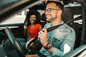 istock Young multiracial couple sitting in a car and fastening seat belts. 1266822025