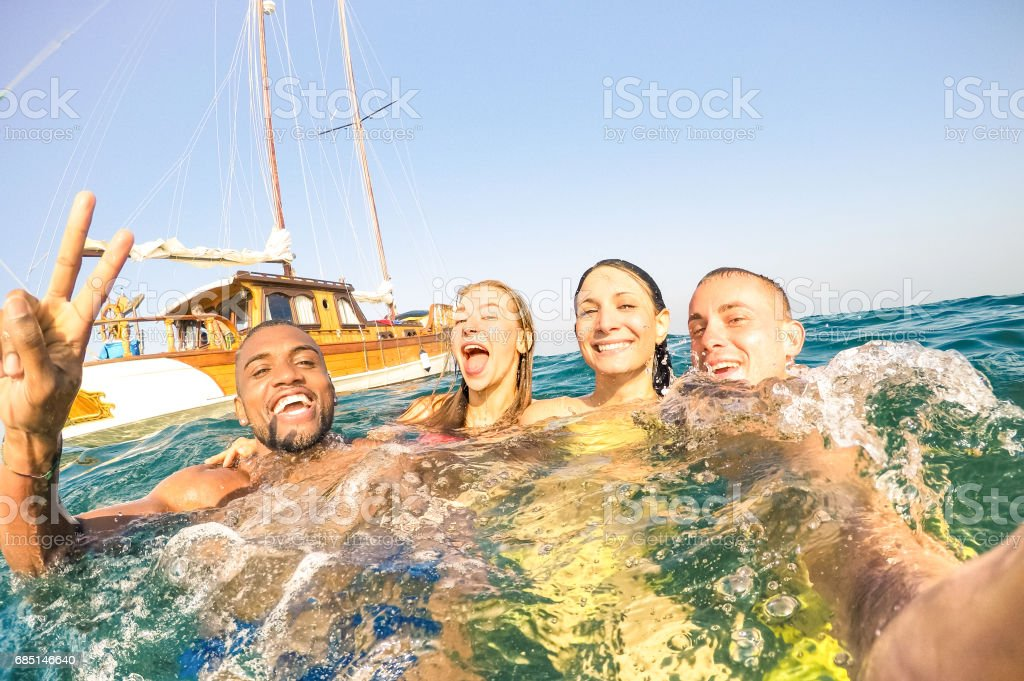 Young multiracial friends taking selfie and swimming on sailing boat sea trip - Rich happy guys and girls having fun in summer party day - Exclusive vacation concept - Bright afternoon  warm filter - foto de stock