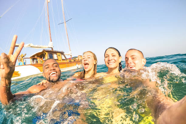 Young multiracial friends taking selfie and swimming on sailing boat sea trip - Rich happy guys and girls having fun in summer party day - Exclusive vacation concept - Bright afternoon  warm filter - fotografia de stock