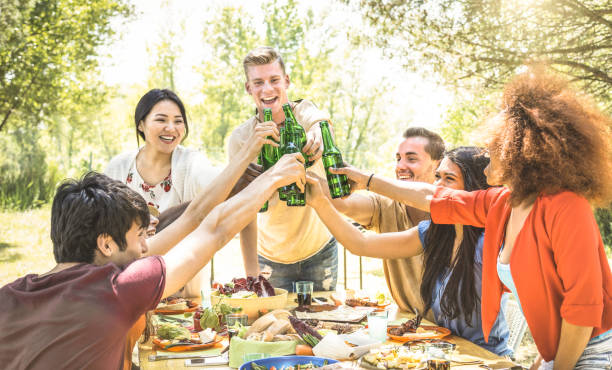 Young multiracial friends toasting at barbecue garden party - Friendship concept with happy people having fun at backyard bbq summer camp - Food and drinks fancy picnic lunch - Focus on beer bottles stock photo