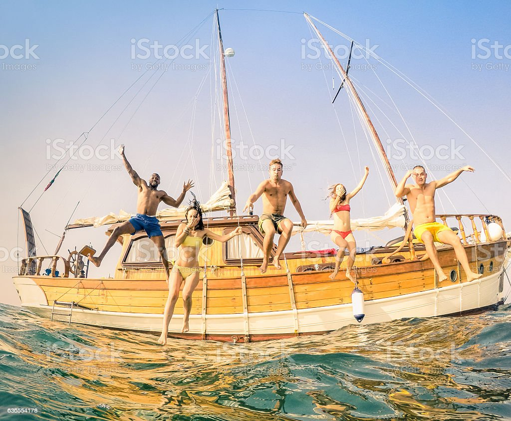 Young multiracial happy friends jumping from sailing party boat foto de stock royalty-free