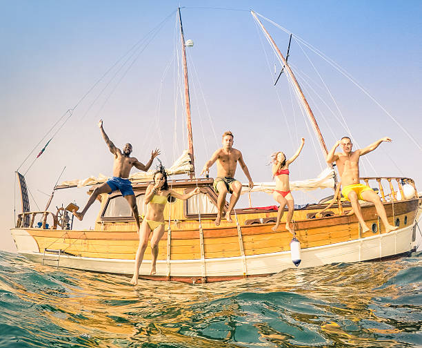 Young multiracial happy friends jumping from sailing party boat stock photo