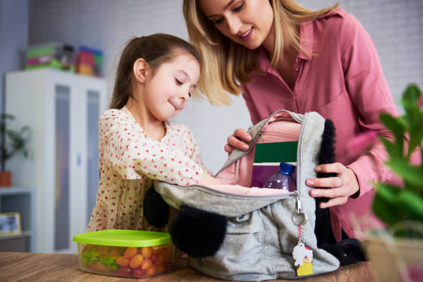 Young mum and daughter packing backpack for the school stock photo