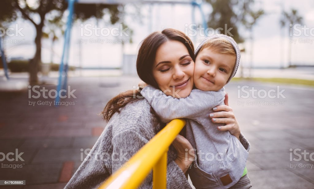 Young mum tenderly hugs young boy at the playground stock photo