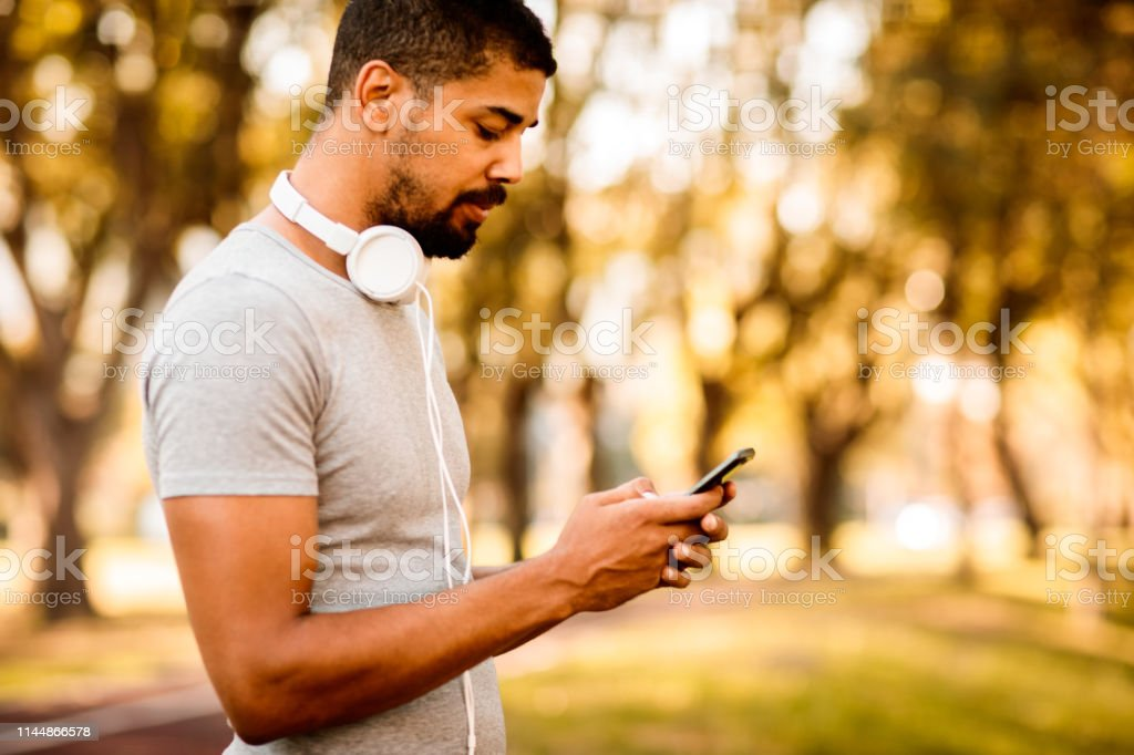 Young athletic man with headphones around his neck using a smart...