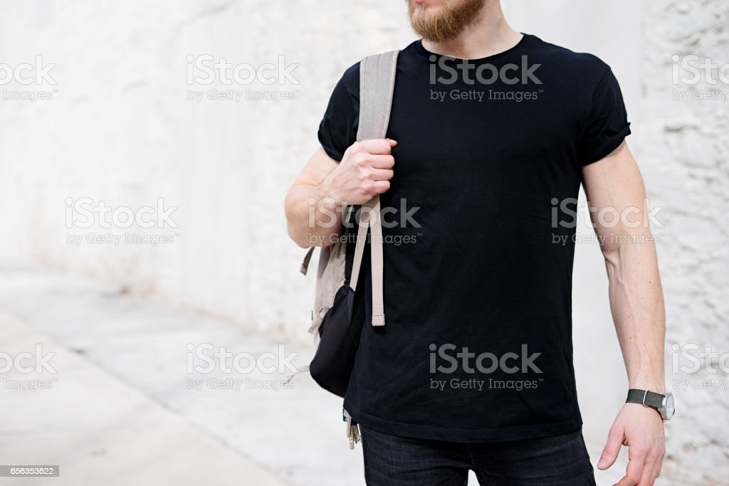 Young muscular bearded man wearing black tshirt and backpack posing outside. Empty white concrete wall on the background. Hotizontal mockup, front view stock photo