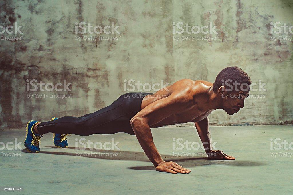 young muscular doing push-ups stock photo