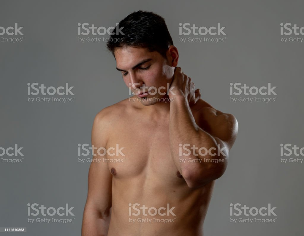 Young muscular fit man touching and grabbing neck and upper back...