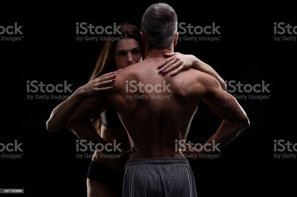 Young muscular man and woman. Sexy couple on black background stock photo