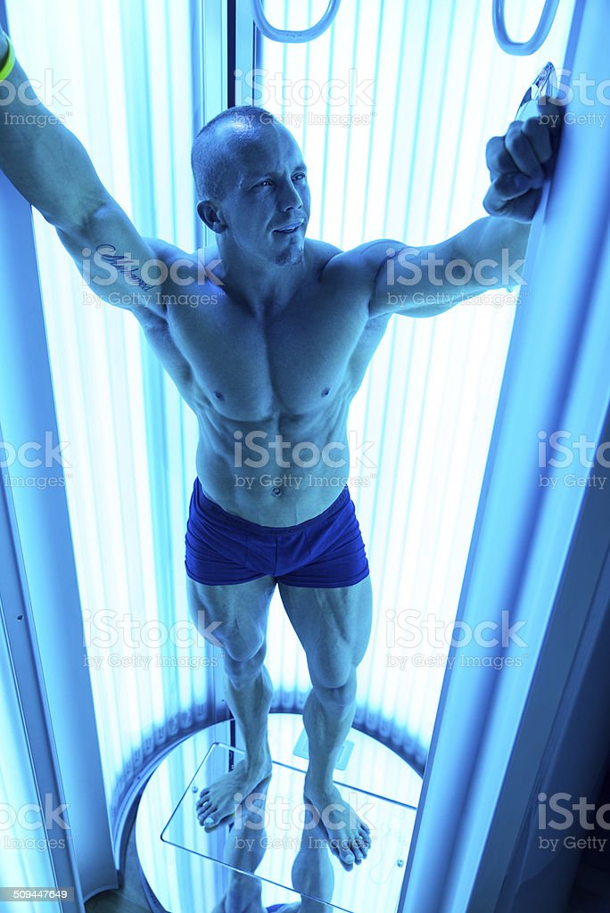 Young Muscular Man At Solarium In Beauty Salon stock photo