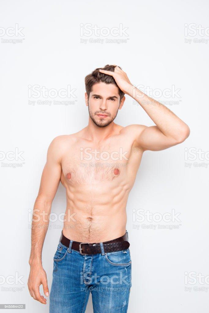 Hombre joven en jeans peinando el cabello con los dedos foto de stock libre  de derechos 59f7275344d
