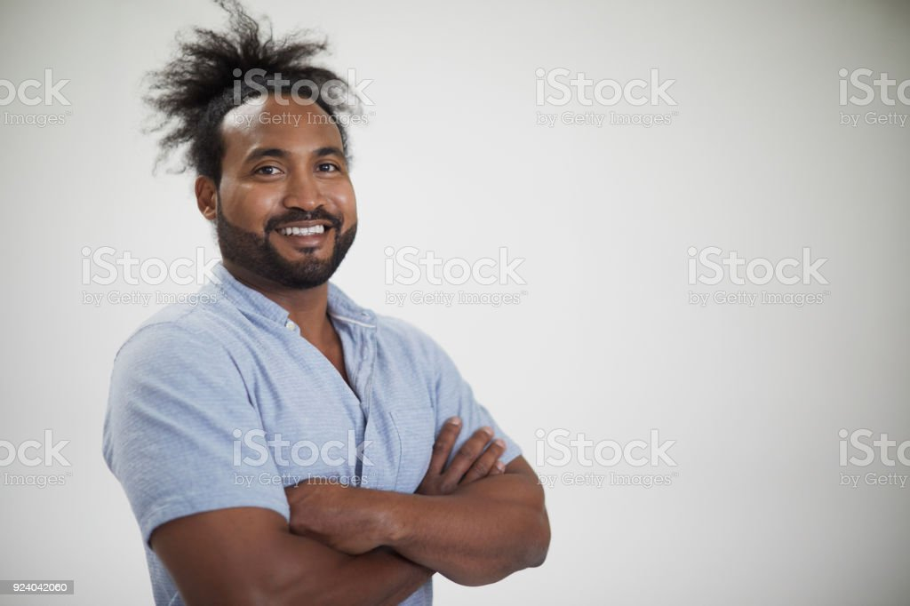 Young muscular man looking at camera on grey background. stock photo
