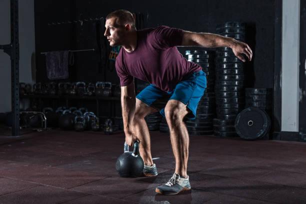 Muskulöse junge Mann Training mit Kettlebells. – Foto