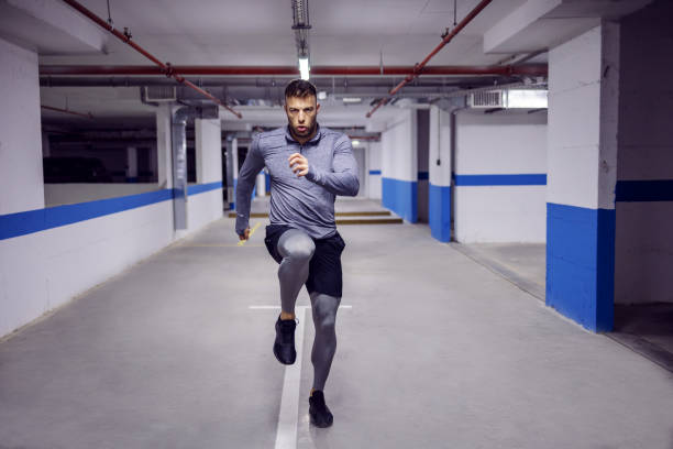 Young muscular sportsman running in place and warming up in underground garage. stock photo