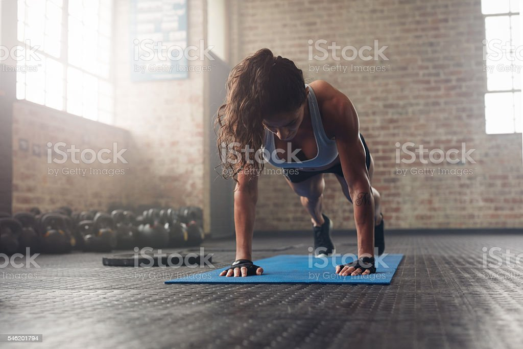 Young muscular woman doing core exercise stock photo