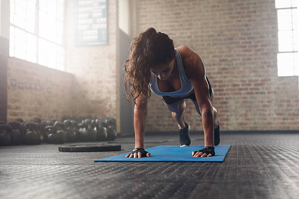 young muscular woman doing core exercise - push up stock photos and pictures