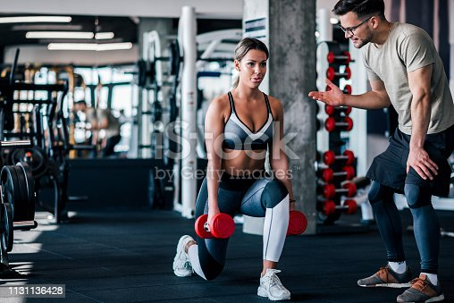 Young muscular woman doing weighted lunge with dumbbells, with personal trainer motivating her.