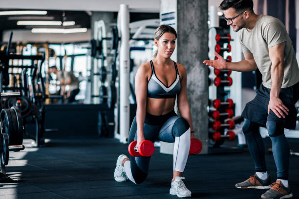 young muscular woman doing weighted lunge with dumbbells, with personal trainer motivating her. - allenatore foto e immagini stock