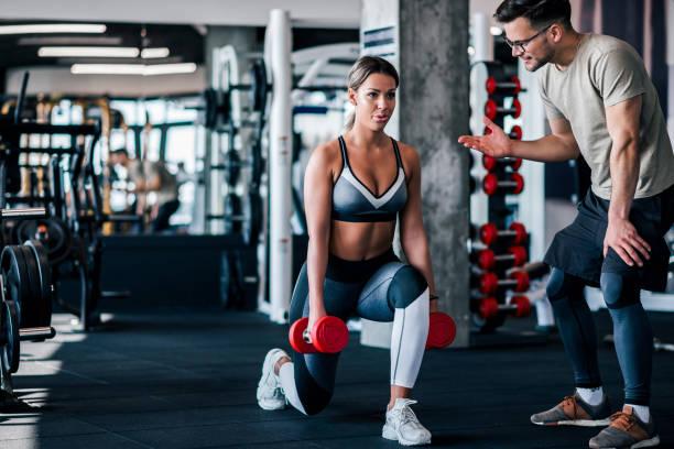 joven mujer musculosa haciendo estocada cargada con pesas, con entrenador personal motivándola. - entrenador personal fotografías e imágenes de stock