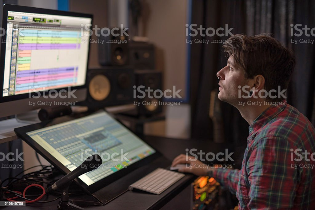 Young music producer working on computer in recording studio. stock photo