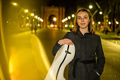 Young musician with her cello in a case in Barcelona streets at night. Light effect made in camera.