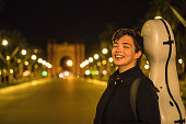 Young musician carrying her instrument in Barcelona.Arc de triomf can be seen, defocused, at background.