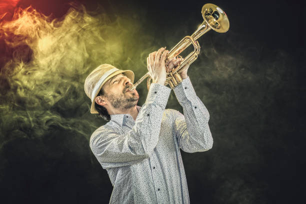 Young musician in straw hat is playing trumpet, vintage, studio shot stock photo