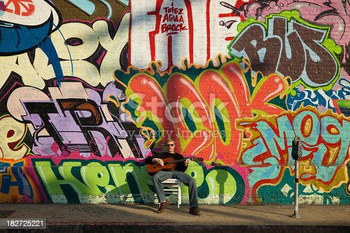 Young man plays classical guitar on sidewalk in front of graffiti brick wall