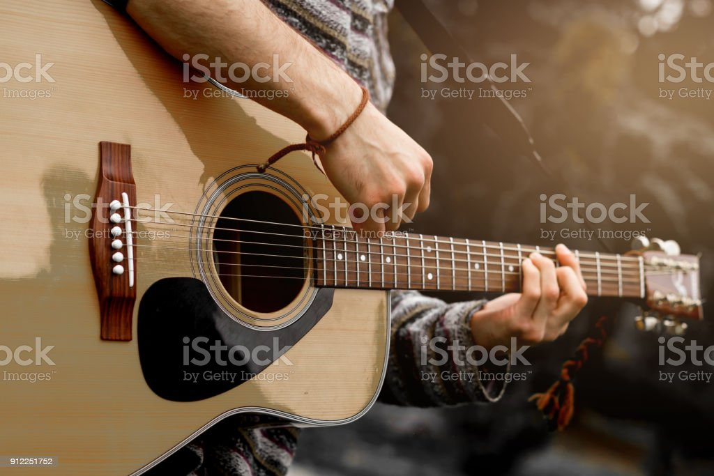 Young musician playing acoustic guitar close up stock photo