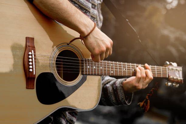 Young musician playing acoustic guitar close up Young musician playing acoustic guitar close up guitarist stock pictures, royalty-free photos & images