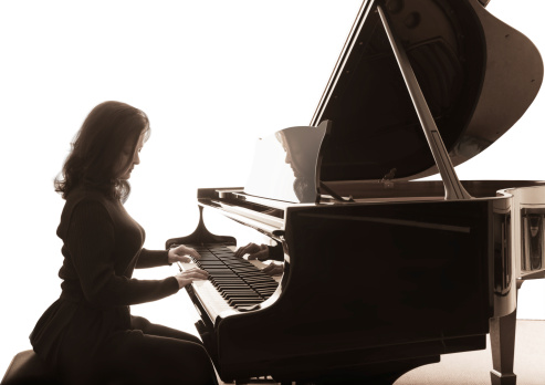 Young musician plays the grand piano