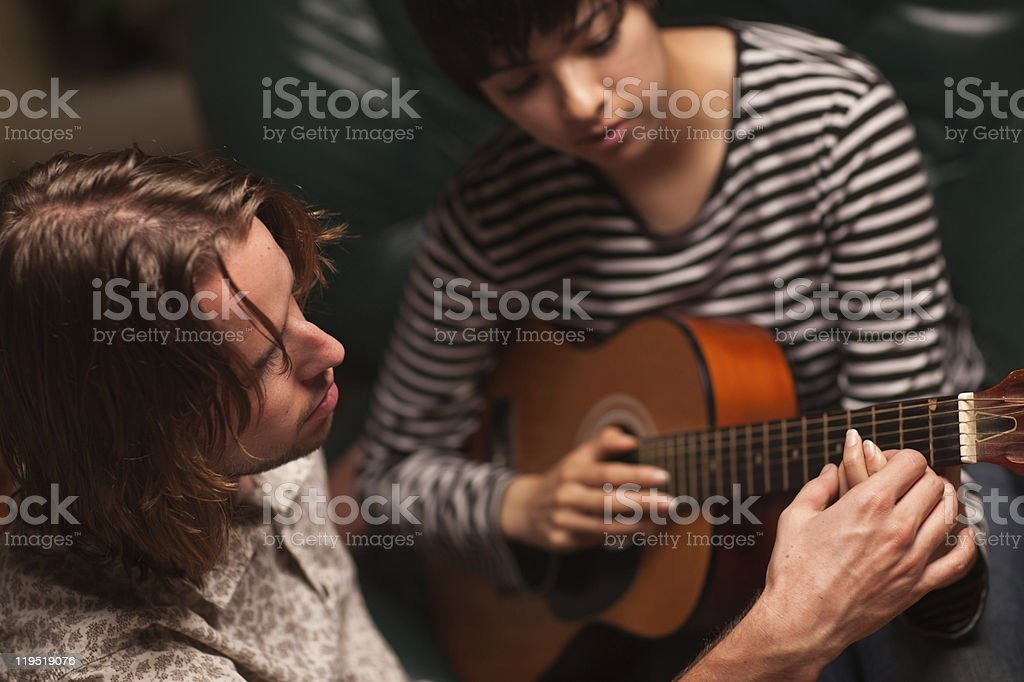 Young Musician Teaches Female Student To Play the Guitar stock photo