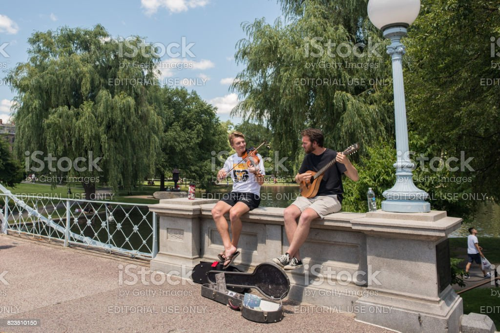 Young musicians play for tips in Boston Public Gardens stock photo
