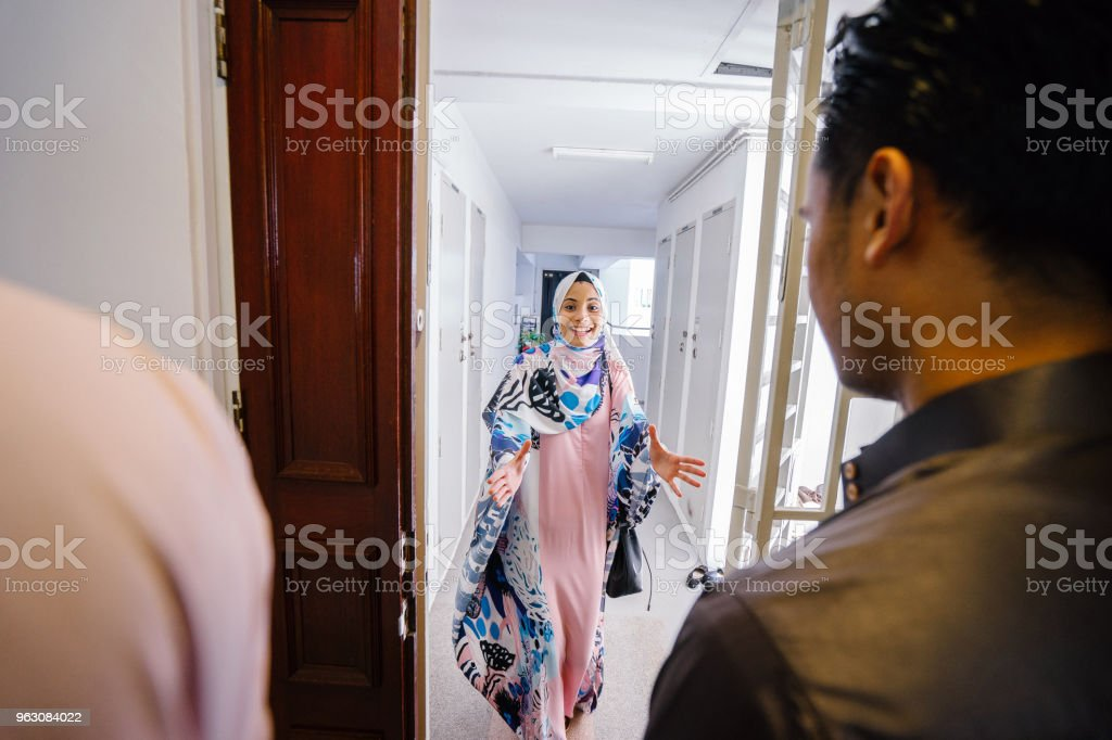 The couple is standing at the entrance of their flat home and are...