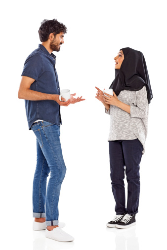 Full length portrait of young muslim couple having friendly chat with a cup of coffee over white background