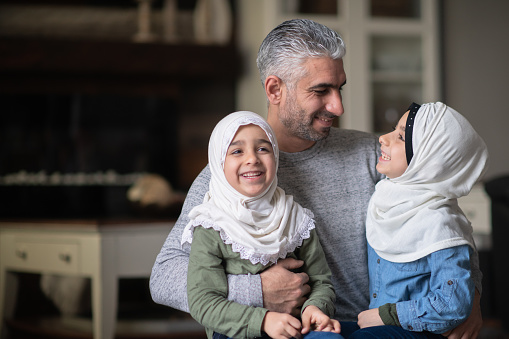 A Young Muslim Girl Enjoying Cuddle Time With Her Dad and Sister