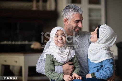 A young ethnic girl is laughing and smiling while interacting with her Muslim dad and sister in their living room.