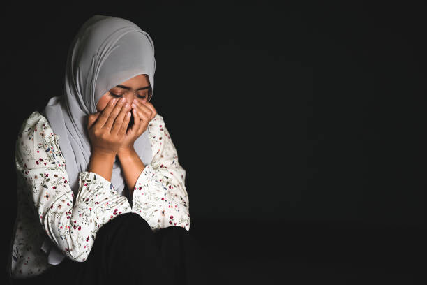 young muslim girl sitting in dark room feeling pain with life problem. crying muslim female holding painful hand, suffering from husband violence - религиозная одежда стоковые фото и изображения