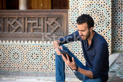 istock Young Muslim man in casual clothing smiling and working on tablet in traditional Arabian ambient 939521508