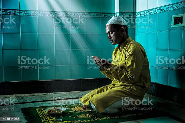 Young Muslim man praying, with folded hands. He is in traditional Indian Attire and sports a skull cap on his head. Sunbeam falling on him.