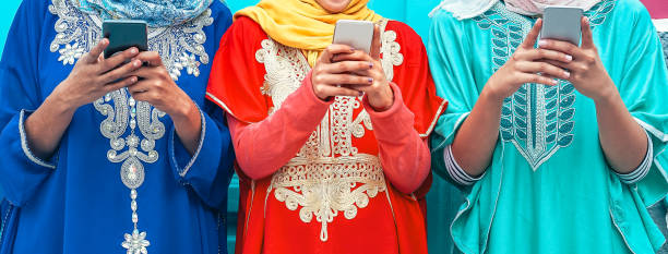 young muslim people using their mobile smart phones in the college - arabian girls addicted to new technology app cellphone for social media - millennial, religion, generation z and technology concept - woman chat video mobile phone foto e immagini stock