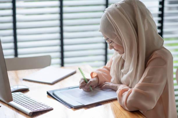Joven estudiante musulmana escribiendo y trabajando en ropa tradicional. - foto de stock