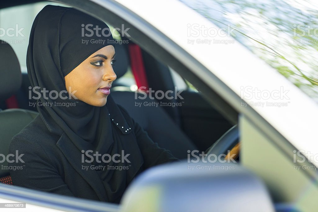 young muslim woman driving a car stock photo